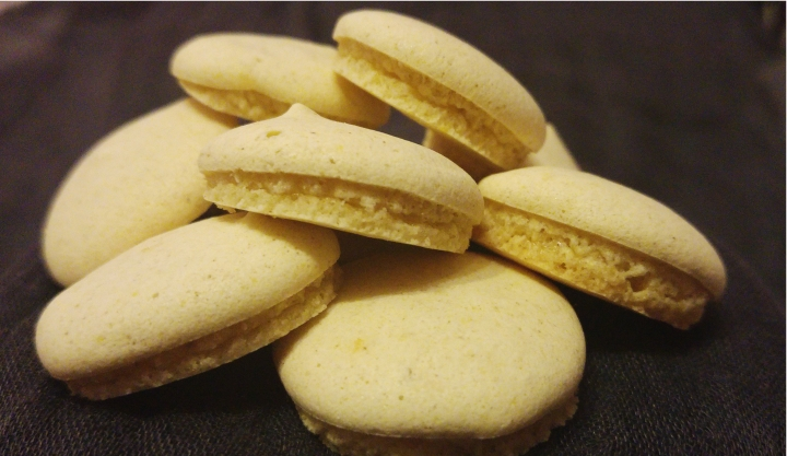 A pile of white, round, small anise cookies