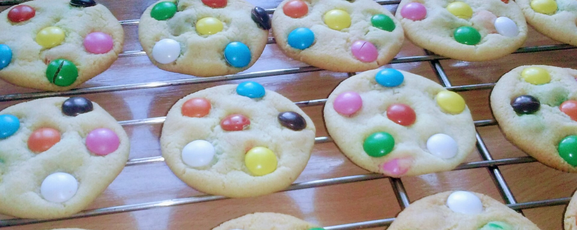 A batch of baked round cookies colourful smarties on a cooling rack