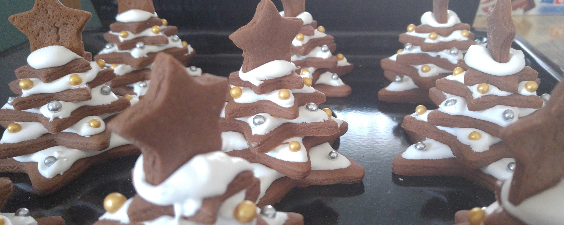 A whole batch of completed gingerbread Christmas trees with icing as snow