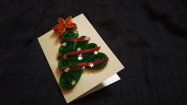 Swirled paper strips forming a green Christmas tree with an orange star, decorated with silver stars