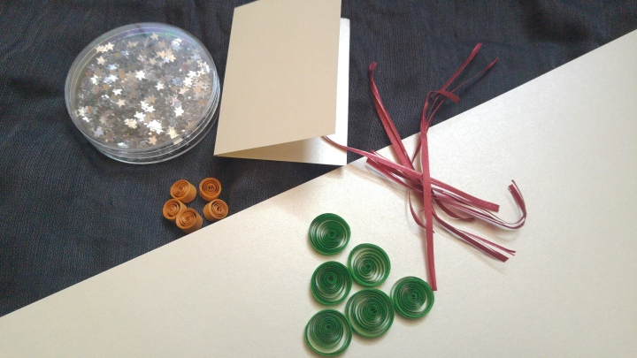Green paper circles, small orange paper circles, an empty gift tag and silver stars
