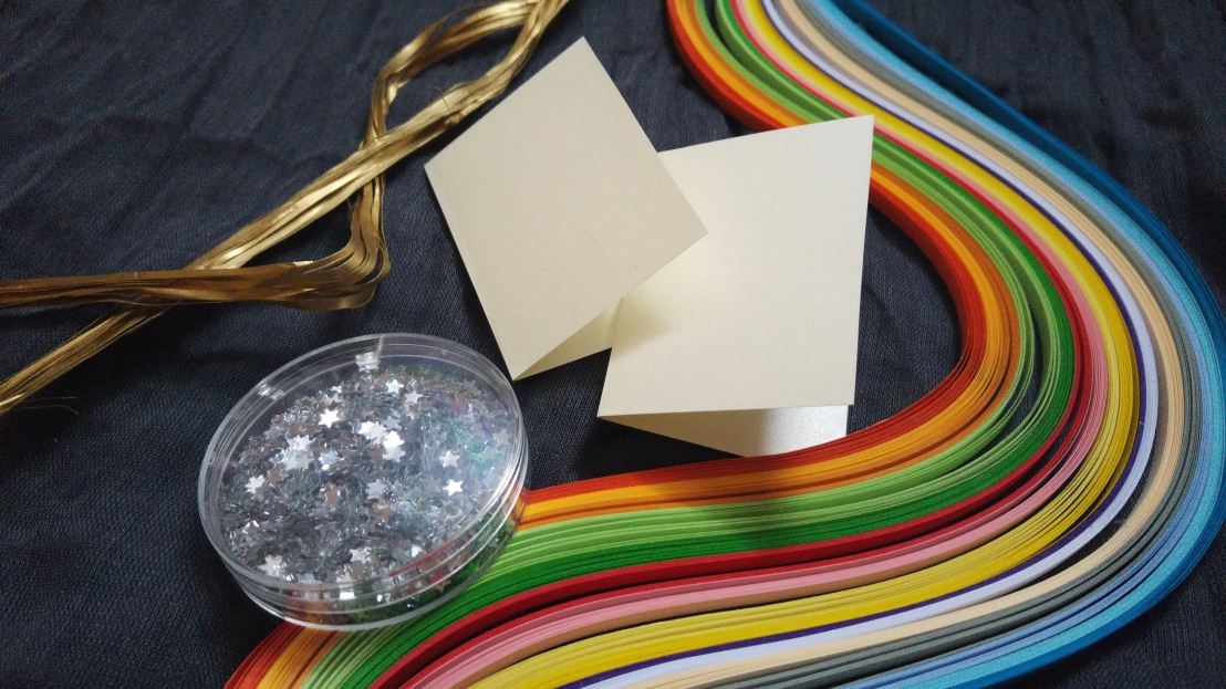 Two empty gift tags, colourful paper strips and silver stars