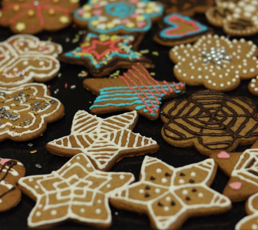Multiple gingerbread cut out cookies decorated with coloured icing and chocolate