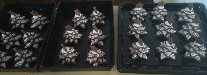 A whole batch of gingerbread Christmas trees on baking trays, with icing as snow
