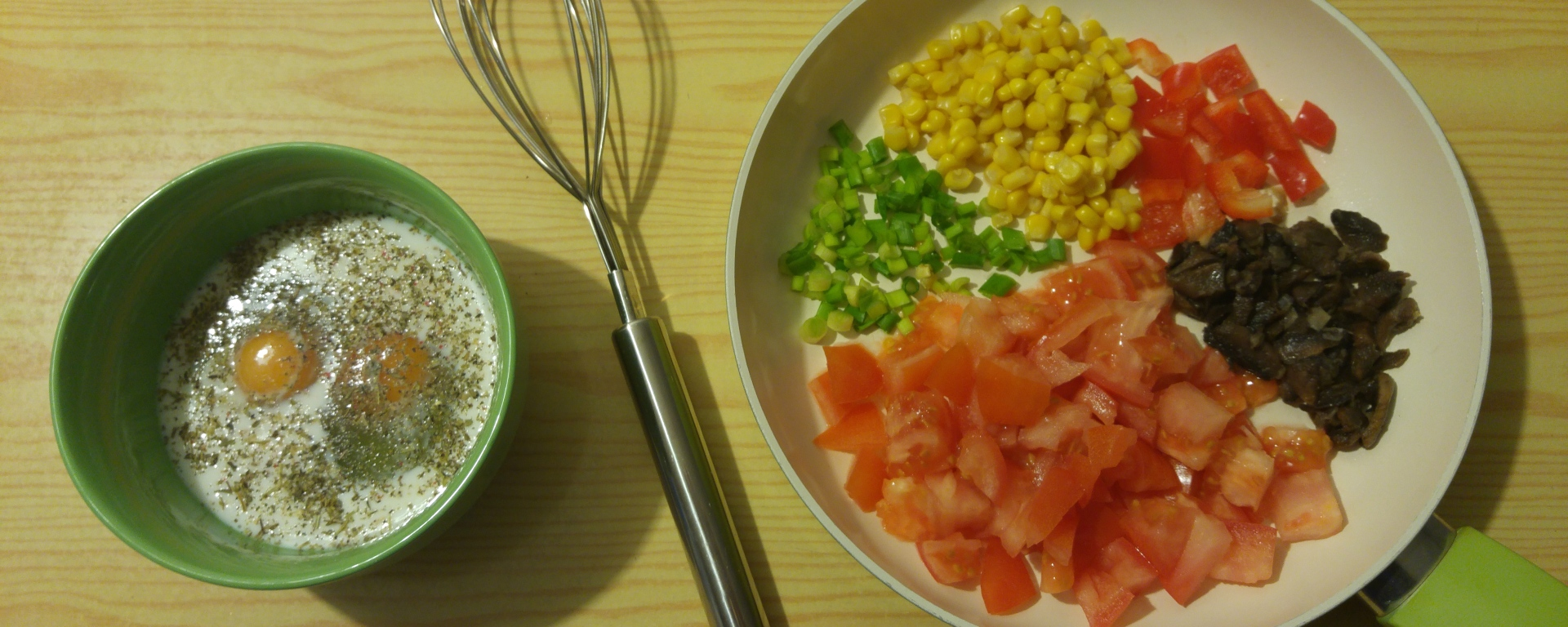 Ingredients for the vegetable omelette - eggs in a bowl and chopped up vegetables on a frying pan