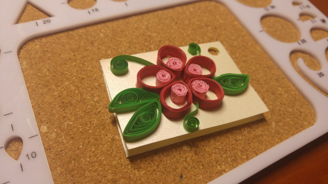 A handmade gift tag - red and pink flower with round petals