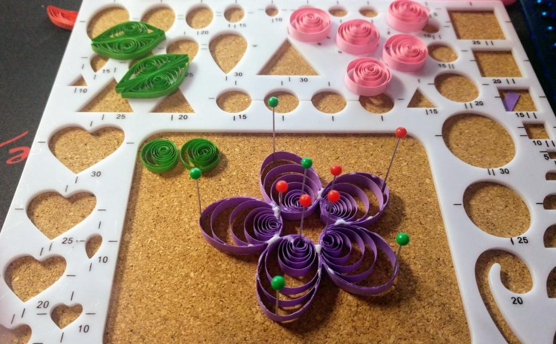 A purple quilling flower in progress