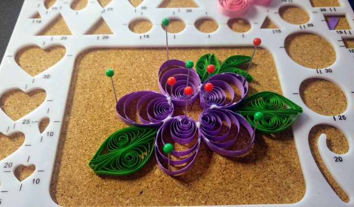 A purple quilling flower in progress on a cork board