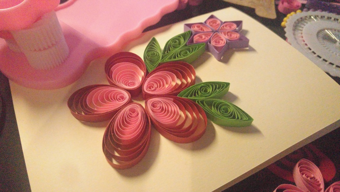 A handmade quilling card in progress - red and pink flower
