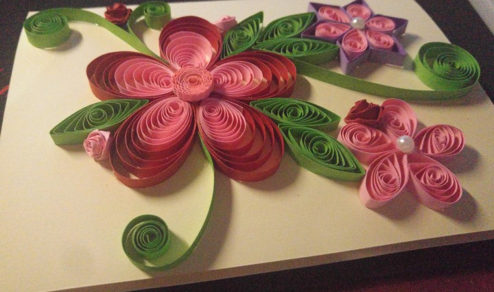 A handmade quilled card - red, pink and purple flowers