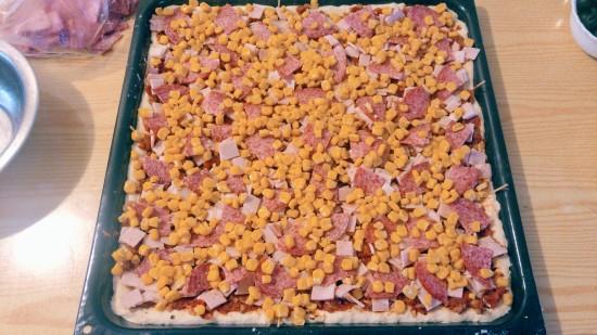 Pizza dough with tomato sauce, ham and corn