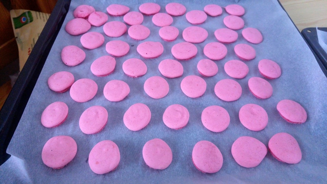 Baked pink small cookies on a baking tray