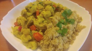 Cauliflower, bell pepper and chickpea curry, on a plate, with quinoa and coriander as garnish