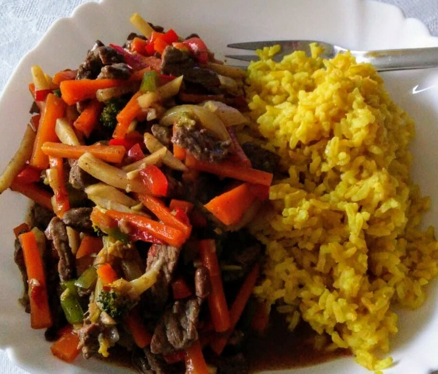 Chinese five spice stir fry on a plate, with yellow rice