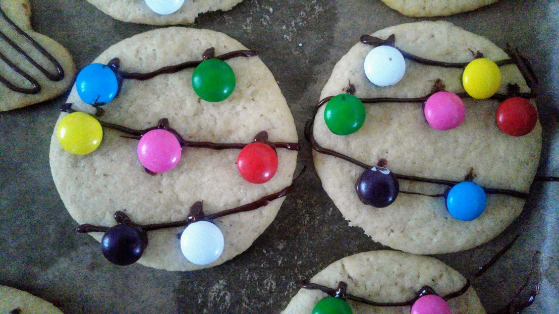 Two round cookies decorated with chocolate (as a string) and smarties (as lights)