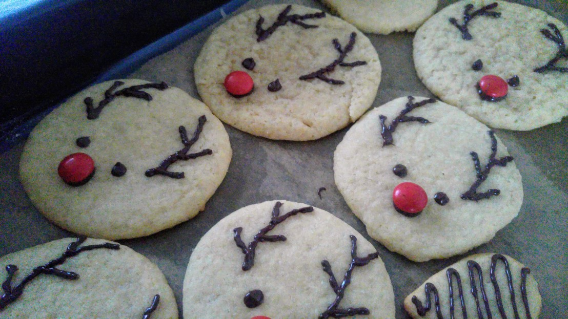 Round cookies with chocolate reindeer faces and red smarties as noses