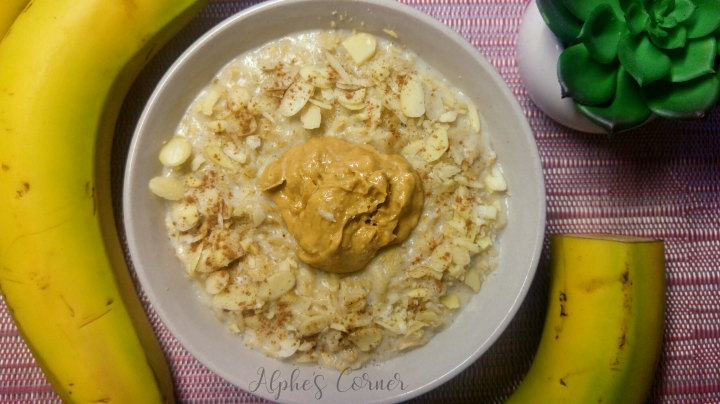 Banana peanut butter porridge in a bowl and bananas for decoration