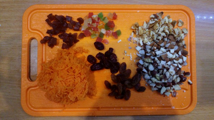 Grated carrot and chopped up nuts and dried fruits on a chopping board