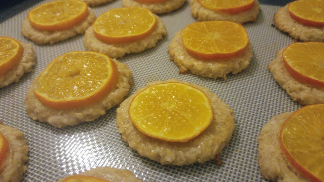 Baked cookies with slices of tangerine, on a baking tray