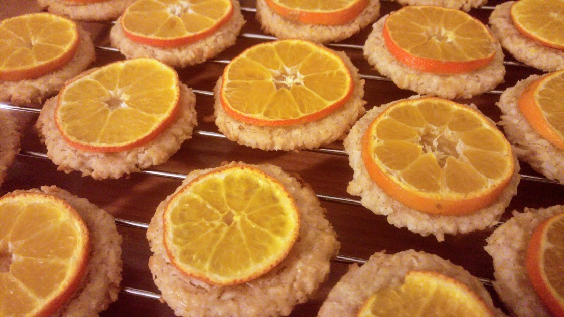 Baked cookies with slices of tangerine, on a cooling rack