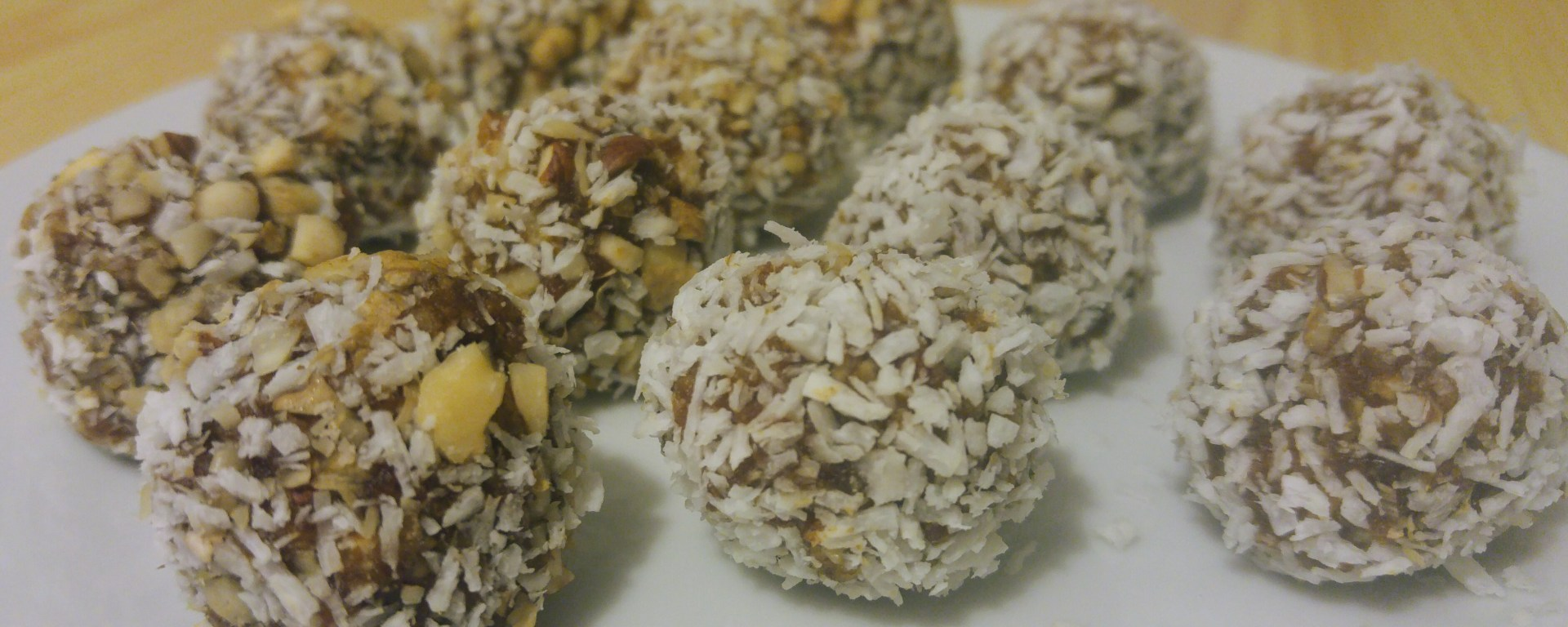 Small date balls covered with coconut, on a plate