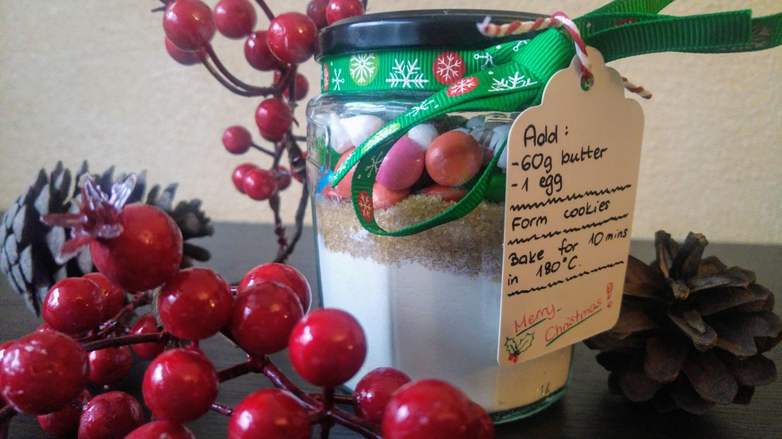 Ingredients for cookies in a big glass jar, with a tag with instructions