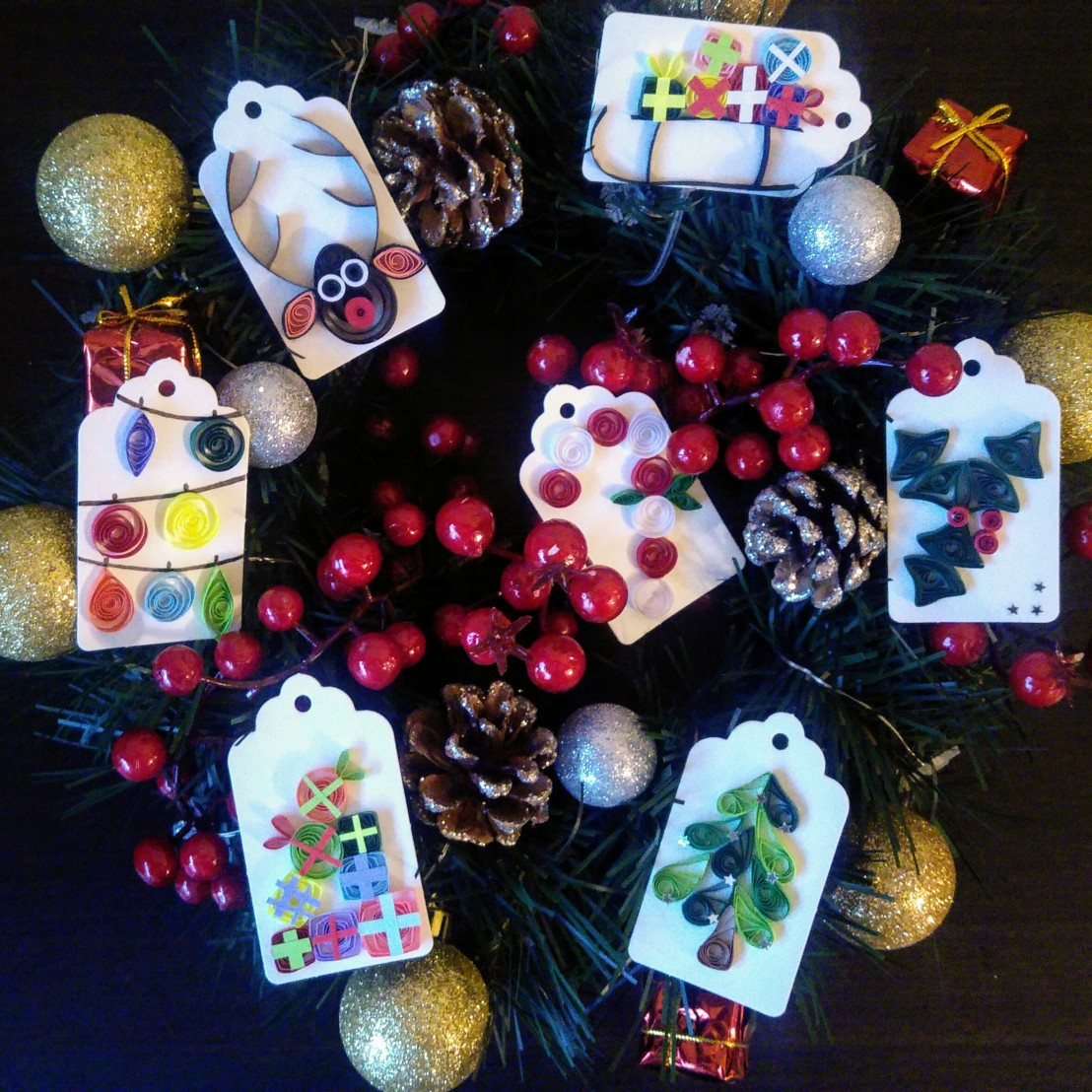 7 quilled handmade Christmas gift tags placed on a Christmas wreath