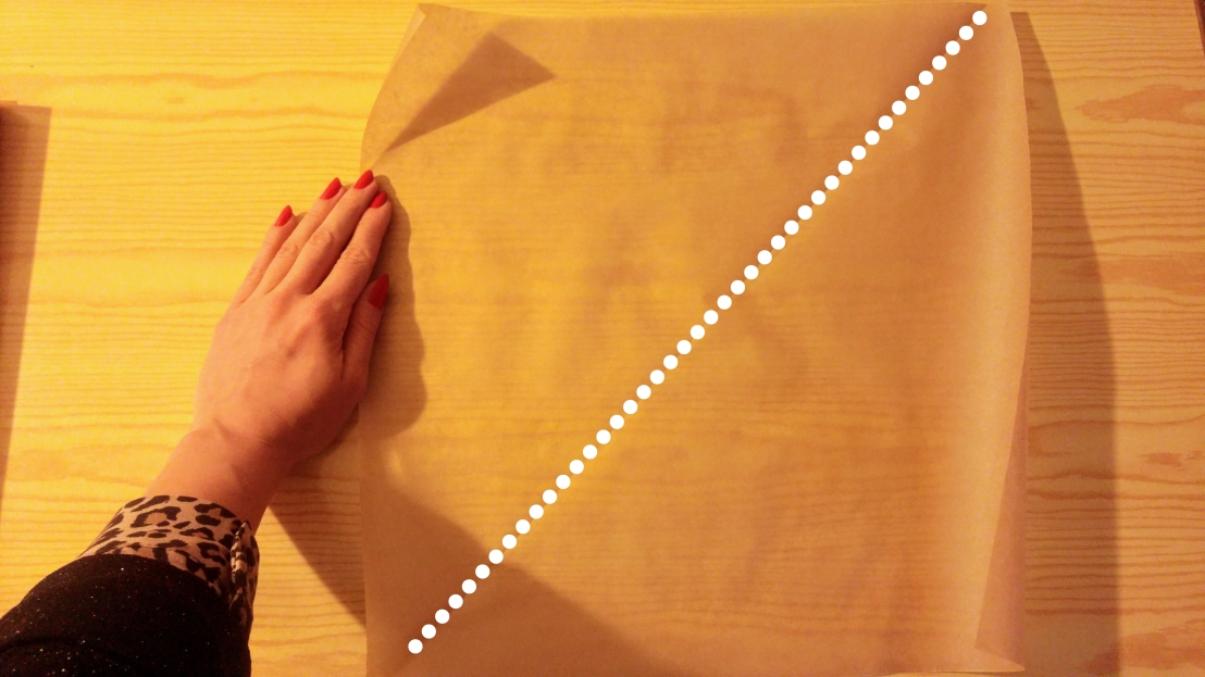 Dividing a square of baking paper into two triangles to make piping cones