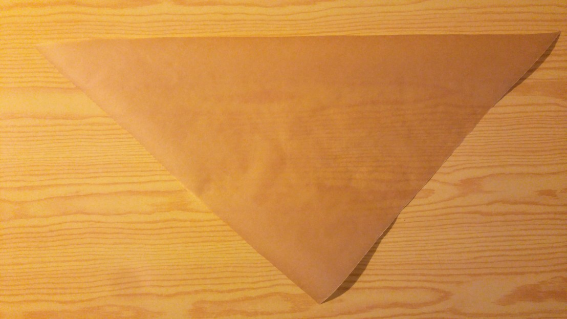 A triangle of paper that will be folded into a DIY piping cone