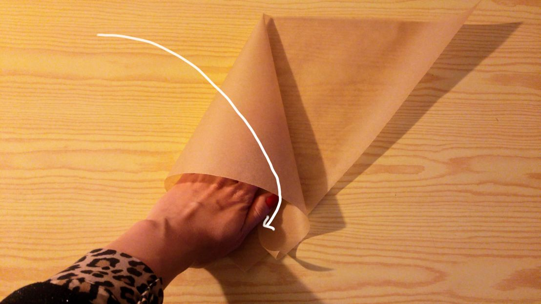 Folding one side of the paper to make a cone