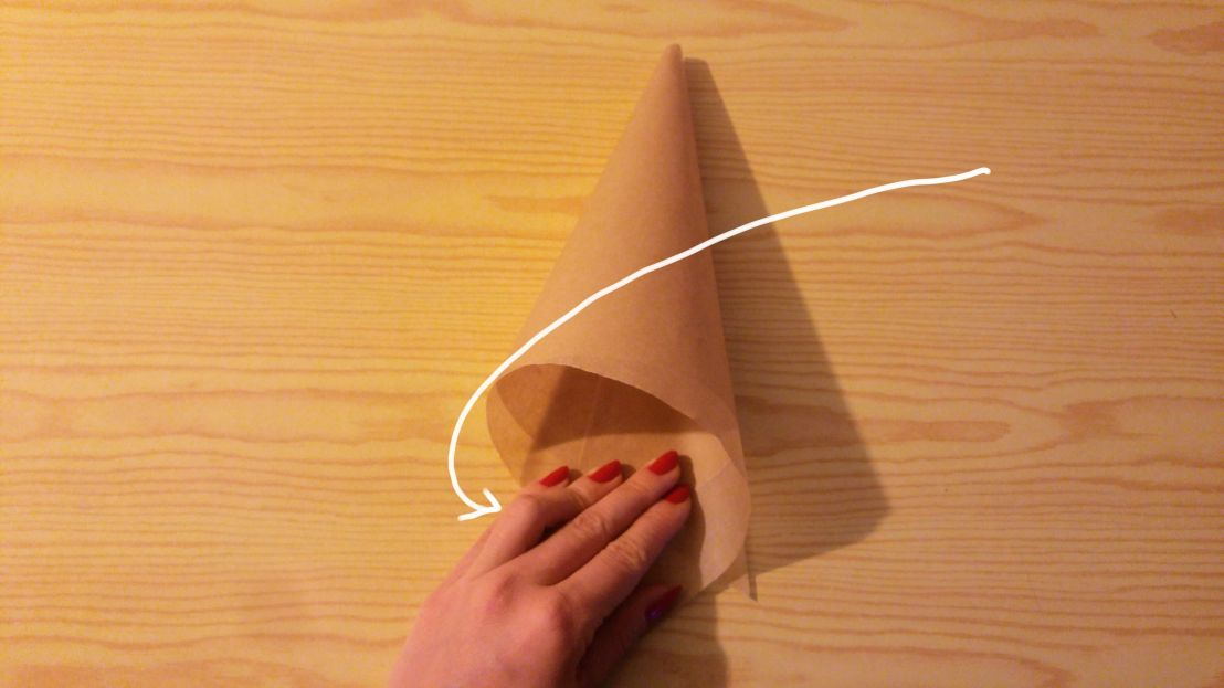 Folding the other side of the paper to make a cone