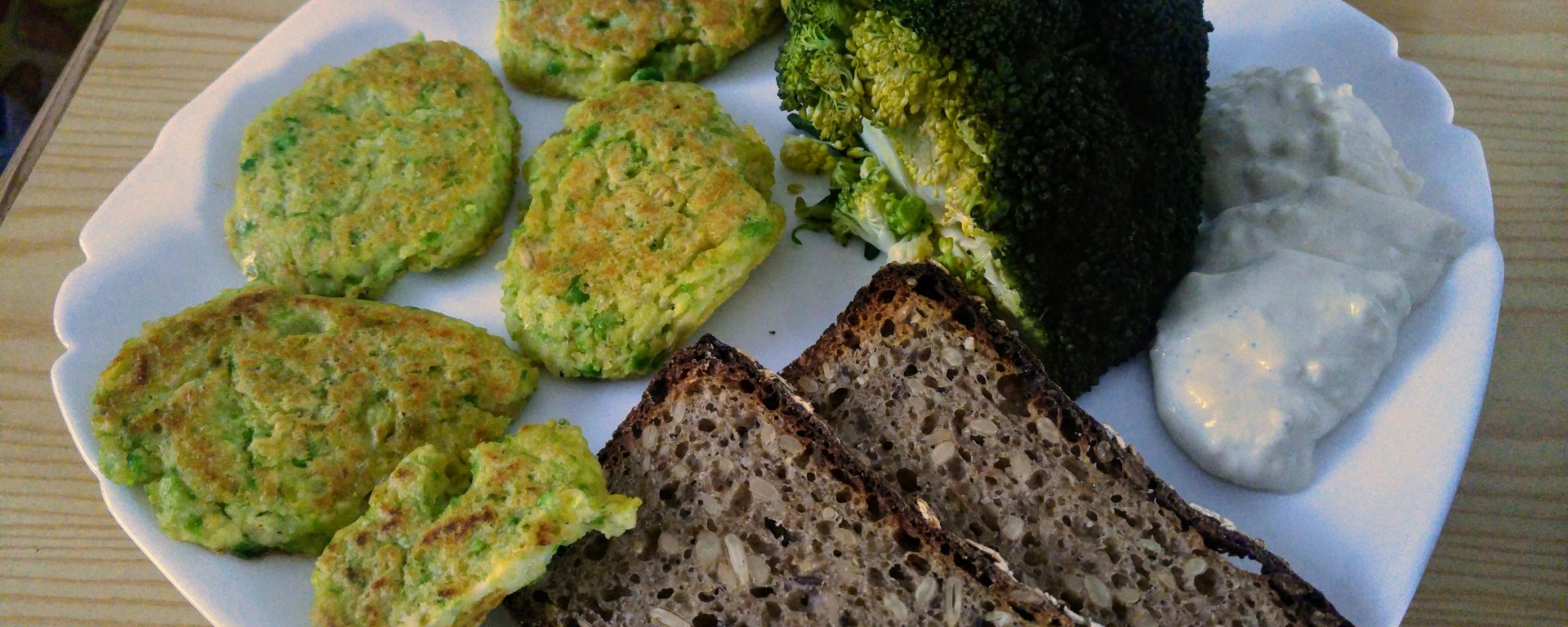 Green peas millet patties on a plate, with broccoli, sourdough bread and garlic sauce