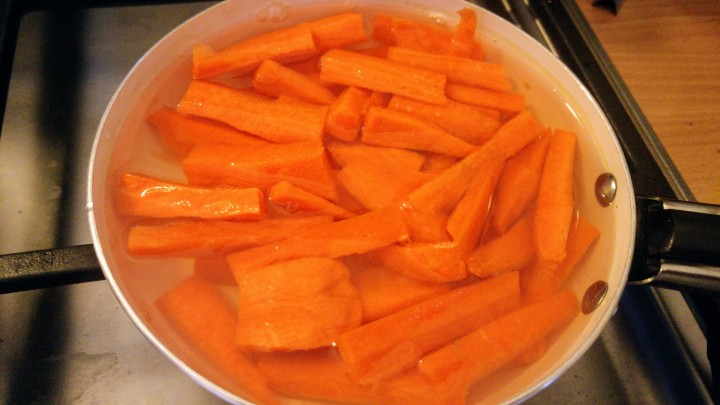 Chopped up carrots in water, on a frying pan