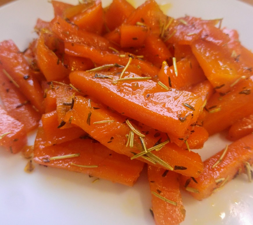 Honey glazed carrots with rosemary on a white plate