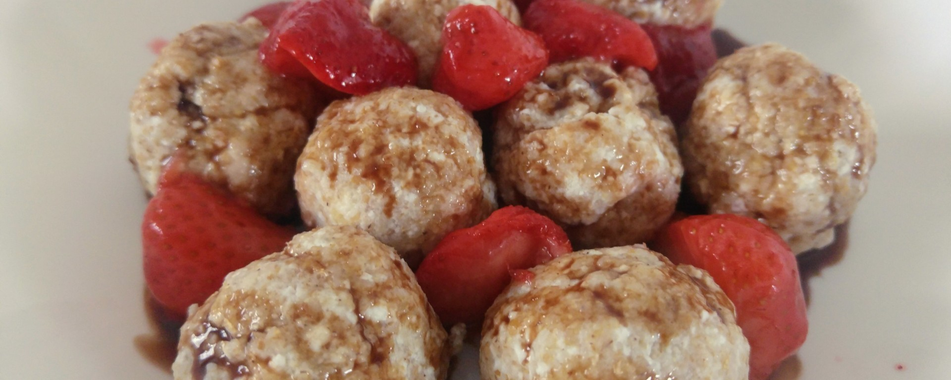 Kopytka - quark cheese dumplings - on a plate with strawberries and chocolate