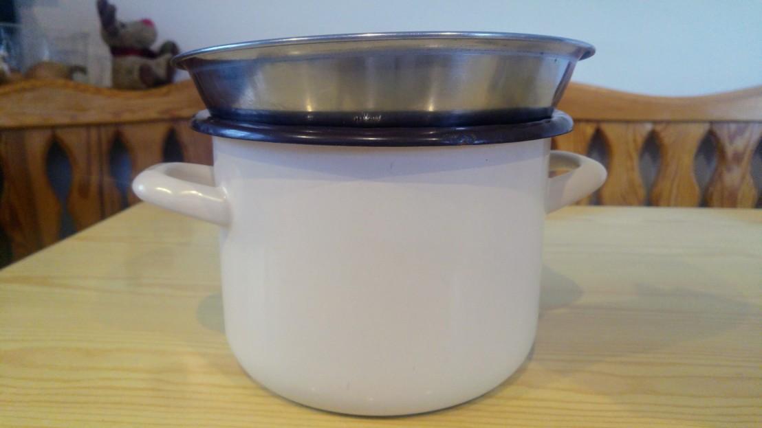 A metal bowl on top of a tall pot