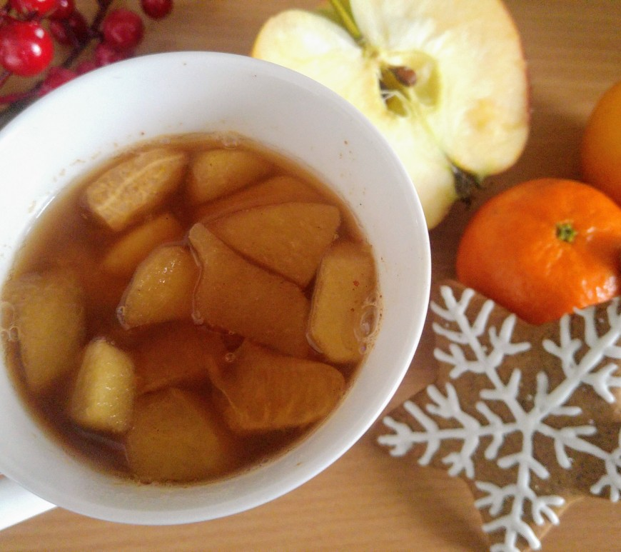 Mulled tea in a mug, decorated gingerbread cookies and fruits