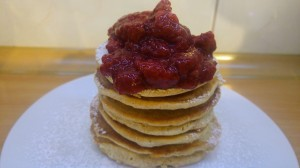 A pile of peanut butter pancakes with strawberry jam on top