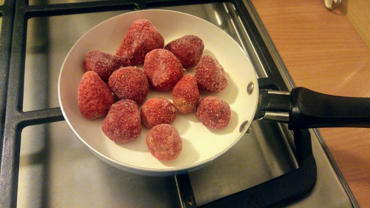 Frozen strawberries on a frying pan