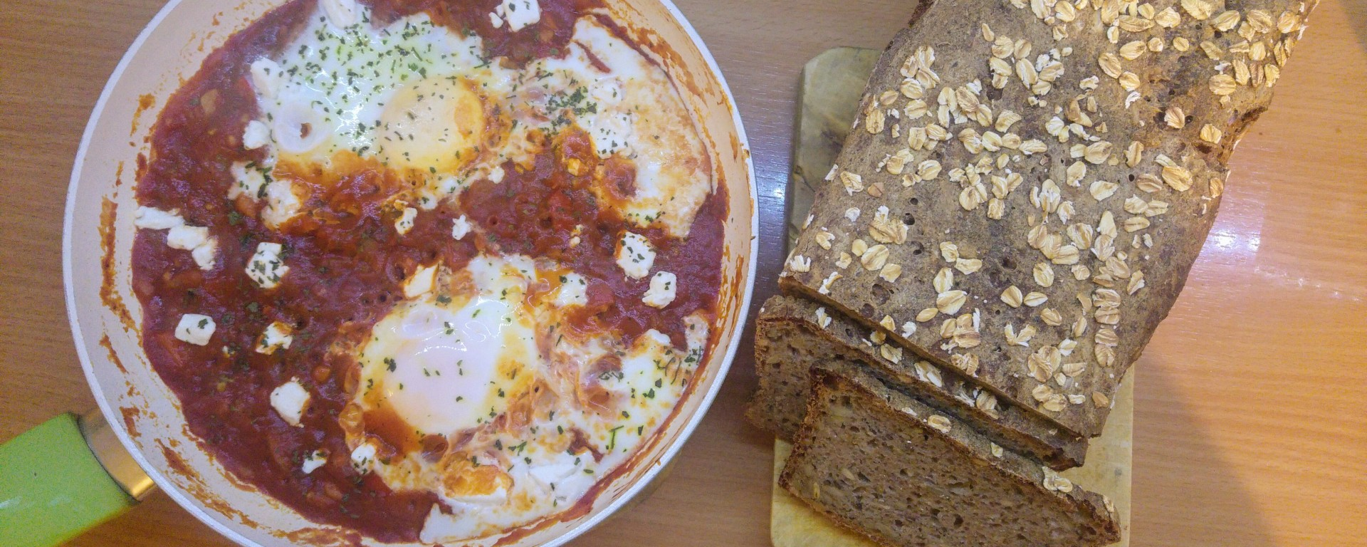 Cooked shakshuka in a pan and a loaf of sourdough bread