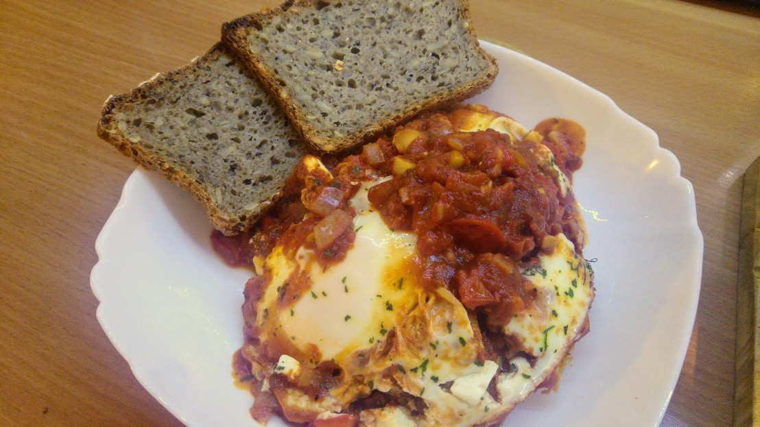 A portion of shakshuka on a plate and two slices of sourdough bread