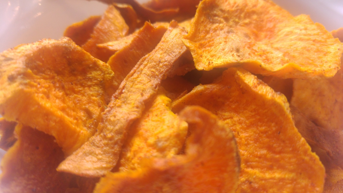 A close up on baked sweet potato crisps in a bowl