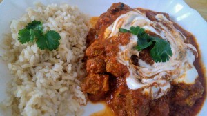 Chicken tikka masala served with rice, garnished with fresh coriander and yoghurt