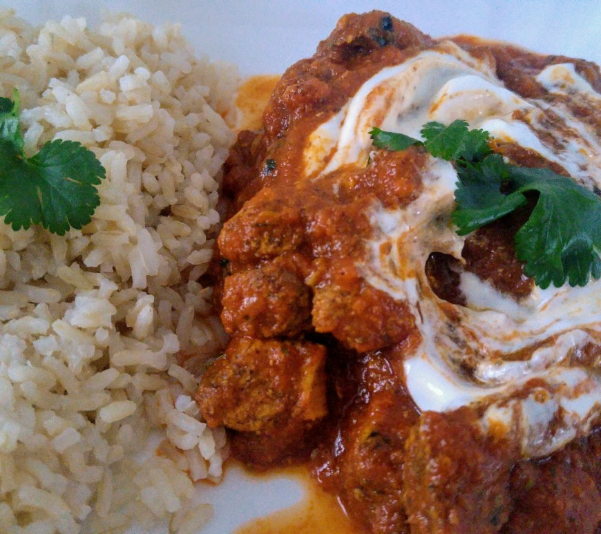 Chicken tikka masala served with rice, garnished with fresh coriander and yoghurt