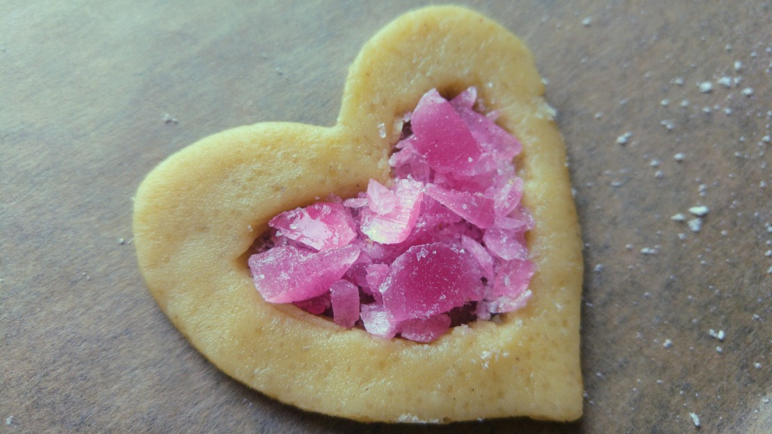 A raw hollow heart shape cookie with crushed pink candy inside, on a baking tray