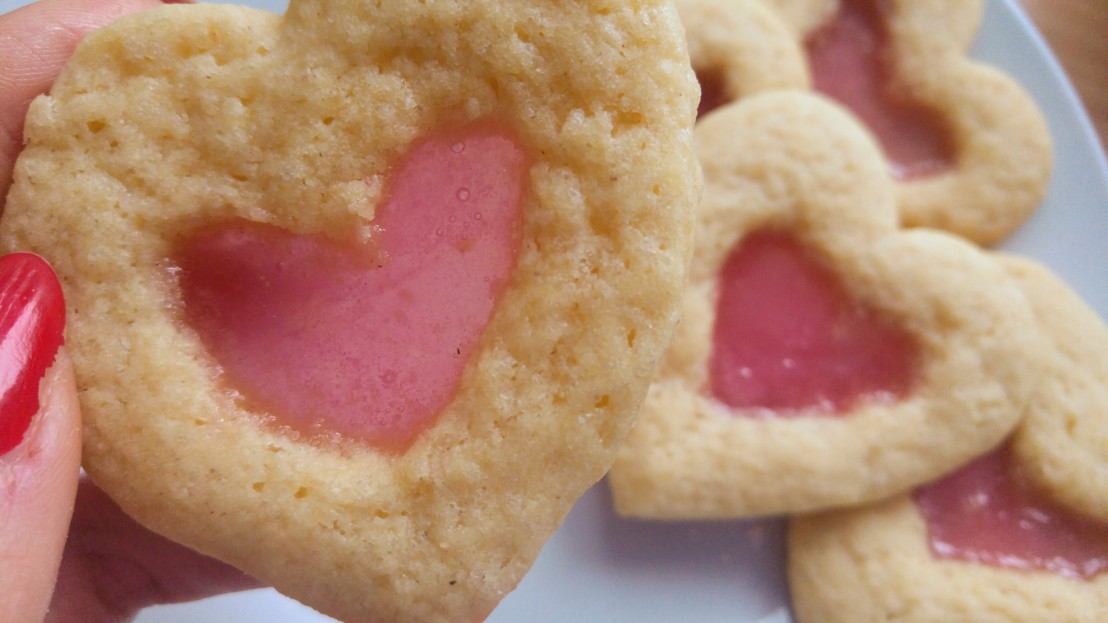 Holding a pink stained glass heart shaped sugar cookie
