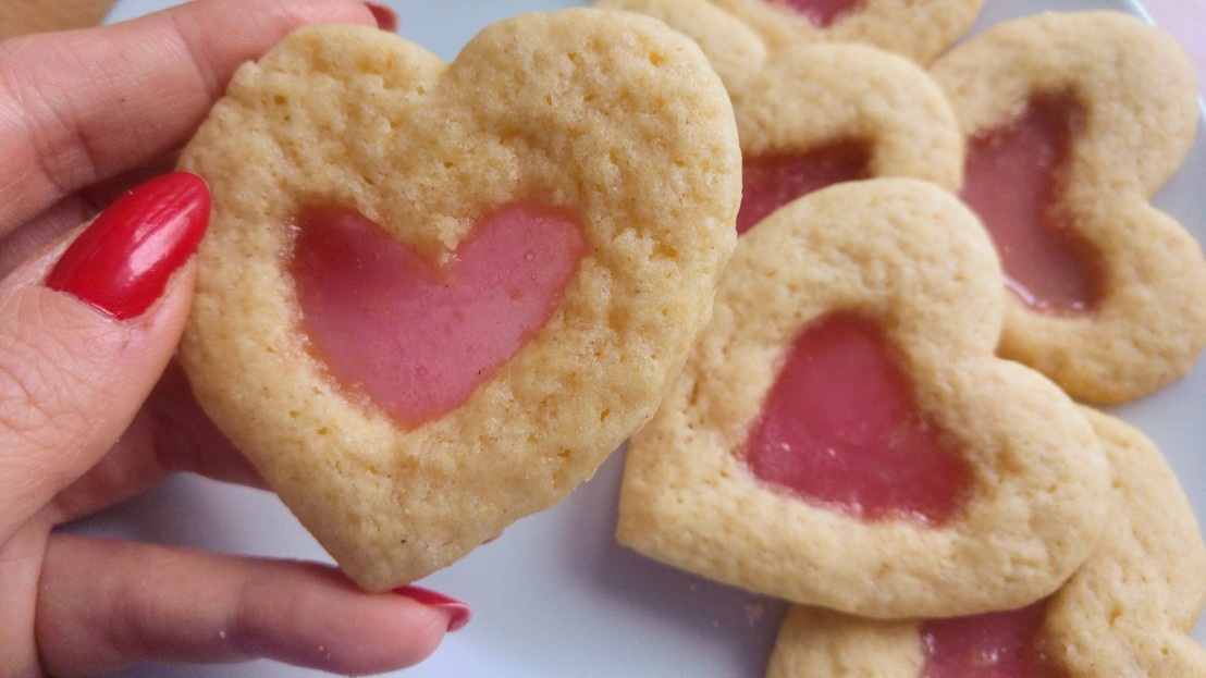 Holding pink stained glass heart sugar cookies