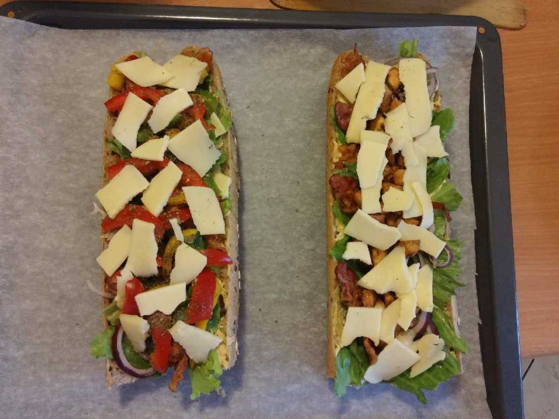 Zapiekanki - two baguettes on a baking tray before cooking