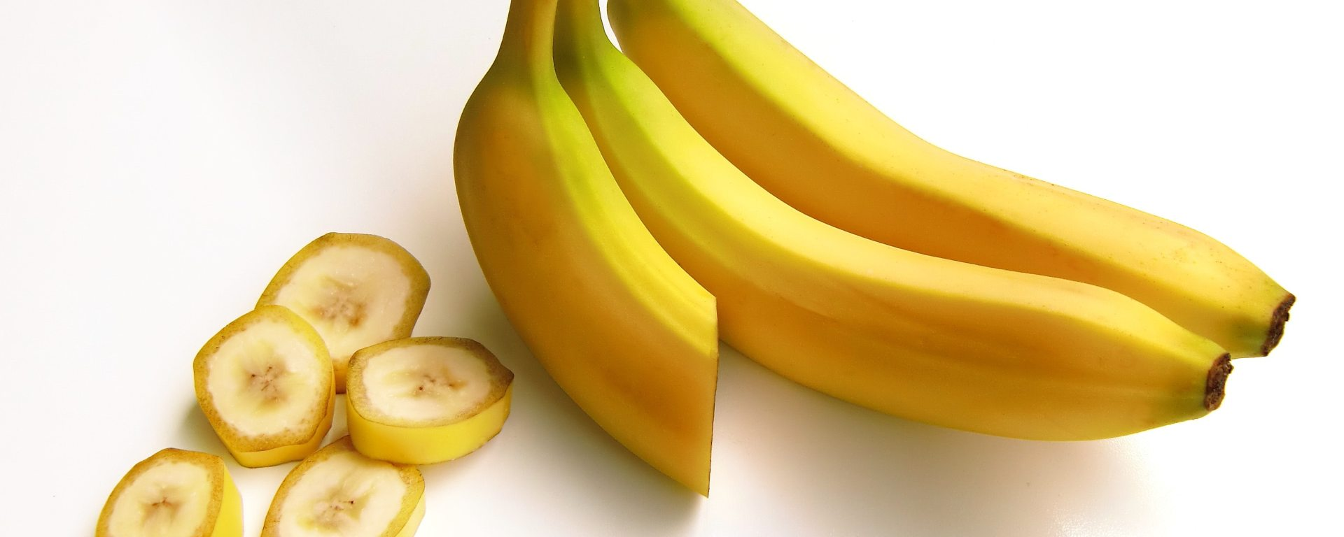 Three bananas next to banana slices