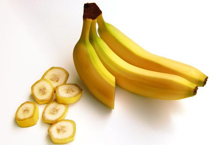 Three bananas next to banana slices